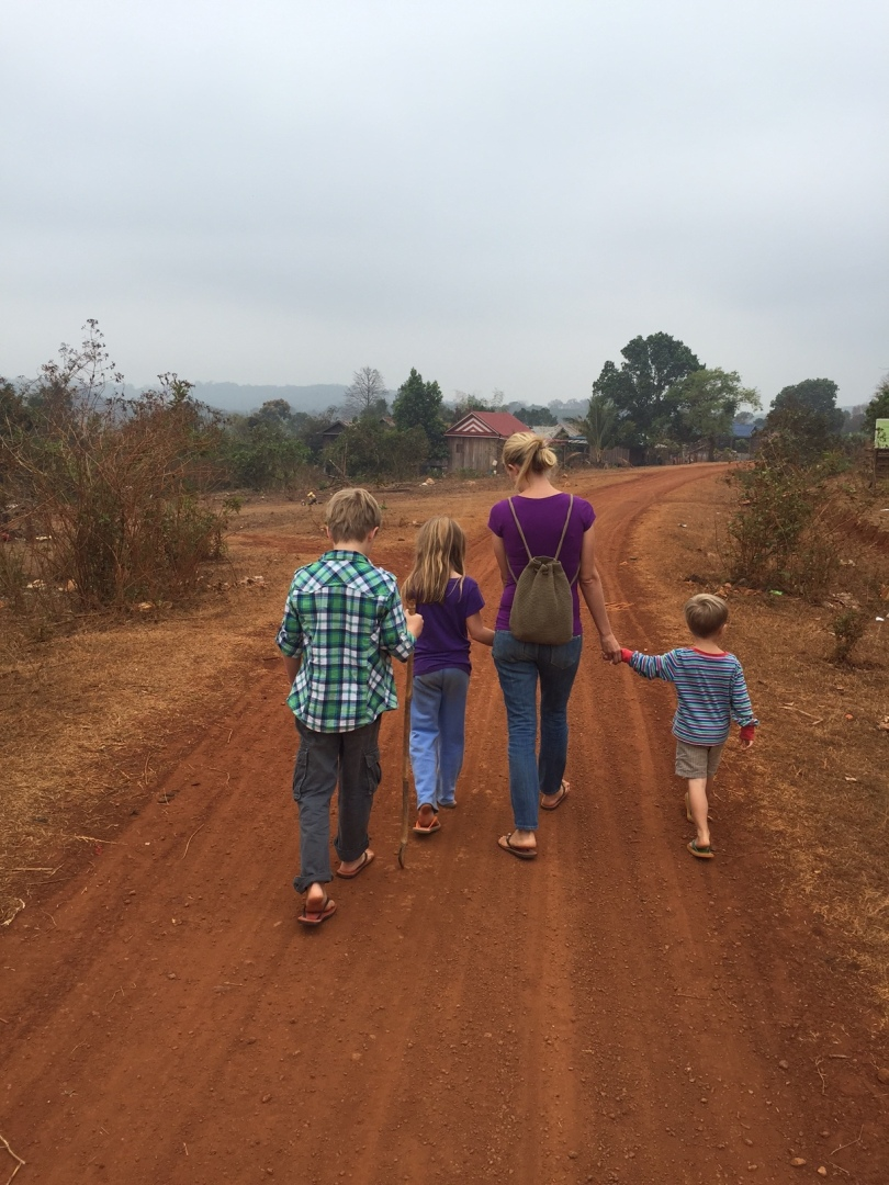 Ann walking with kids in village